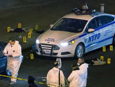 Bulletproof vests lie on each side of an NYPD patrol car as investigators work at the scene where two NYPD officers were shot in the Bedford-Stuyvesant neighborhood of the Brooklyn borough of New York on Saturday, Dec. 20, 2014. Police said an armed man walked up to the officers sitting inside the patrol car and opened fire before running into a nearby subway station and committing suicide.