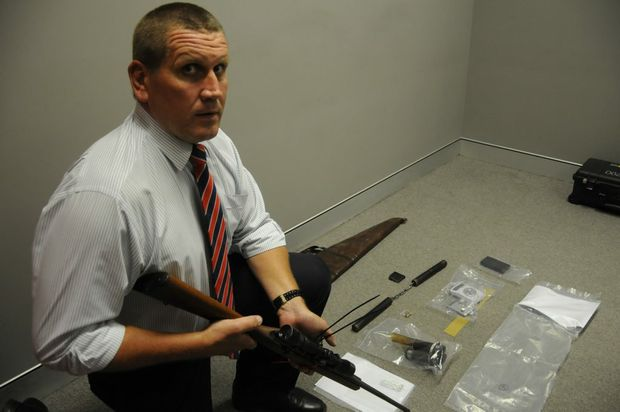 Toowoomba Criminal Investigation Branch acting officer in charge Detective Acting Senior Sergeant Brian Collins inspects a rifle and other items seized during raids on properties in Toowoomba, the Darling Downs and Lockyer Valley.