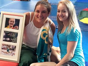 SURPRISED: Olympic gymnast Larrissa Miller presents Ballina RSL Youth Club's Claudia Weston with an Olympic leotard and signed photos.