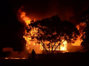 UP IN FLAMES: Dalby firefighters douse a Bunya St house fire on Saturday morning.