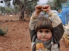 THIS photo of a Syrian child staring into a camera lens believing it was a gun barrel and raising her arms in surrender has  been shared around the world.