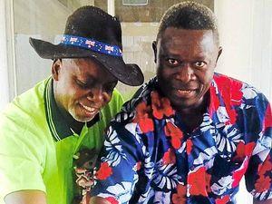 CELEBRATION: Denis Kabamba (left) and Charles Kitapindu cut the pavlova at their celebratory morning tea at Mercy Community Services.