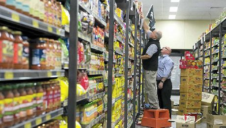 BACK IN BUSINESS: Peter Nisbet (left) and Scott Mourant of Taste of India stock the shelves before the IGA Supermarket's grand opening.