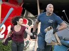 Carla Gugino and Dwayne Johnson in a scene from the movie San Andreas and (right) on set.