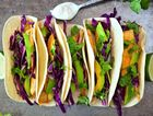 Fish tacos with red cabbage lime slaw on rustic tray