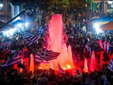 Supporters of the Syriza party and No vote campaign wave flags and react after results of