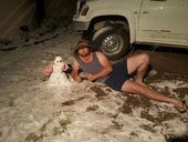 WHERE else but Queensland would a snow photo feature a man in shorts and singlet, lying next to a snowman with a tea towel for a neck scarf.