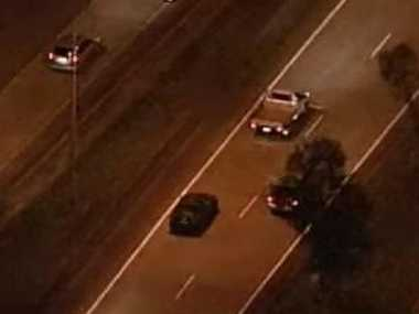 Police follow the black car in a chase that began about 5.10pm. Photo: Nine News