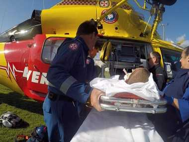 Westpac Rescue Helicopter crew load an 11-year-old boy with suspected spinal injuries into the helicopter.