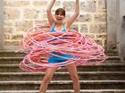 AN AUSSIE fitness fanatic has hula hooped her way into the Guinness World Records by spinning 181 of the plastic loops at once.