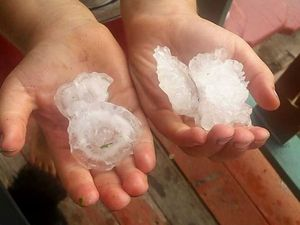 Sha Sha Atkins shows the size of the hail in Oakey.