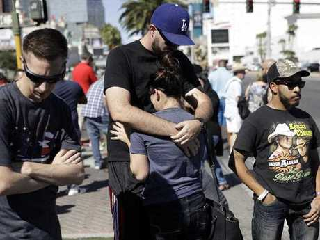 Reed Broschart, center, hug his girlfriend Aria James on the Las Vegas Strip in the aftermath of a mass shooting at a concert Monday, Oct. 2, 2017, in Las Vegas. The couple, both of Ventura, Calif., attended the concert.