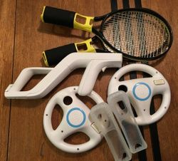 Tennis racquets x2, steering wheels x2, rifle, silicon controller covers x2. No controllers included...