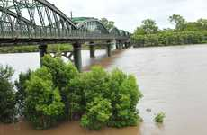 The swirling, muddy floodwaters of the Burnett River in Bundaberg slowly rise higher each day.