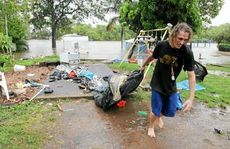 Jason Baas helps remove belongings from a site at the Riverdale Caravan Park, Bundaberg North.