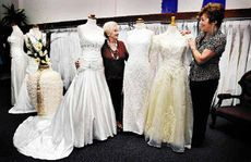 Comparing the changing style of wedding gowns over the years at Mary Vidler Bridal Gowns in Lismore are former owner Mary Vidler (left) and current Janelle Power.
