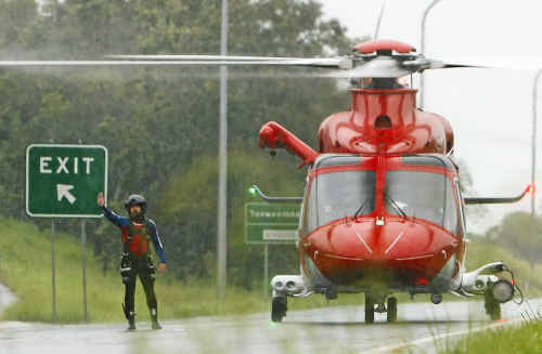 An EMQ AW139 helicopter lands on the Warrego Highway during the January floods, awaiting access to Amberley for refuelling before returning to Grantham for rescue services.