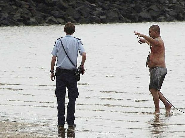 Police apprehend Eric Heuer at Urangan beach after the attack.