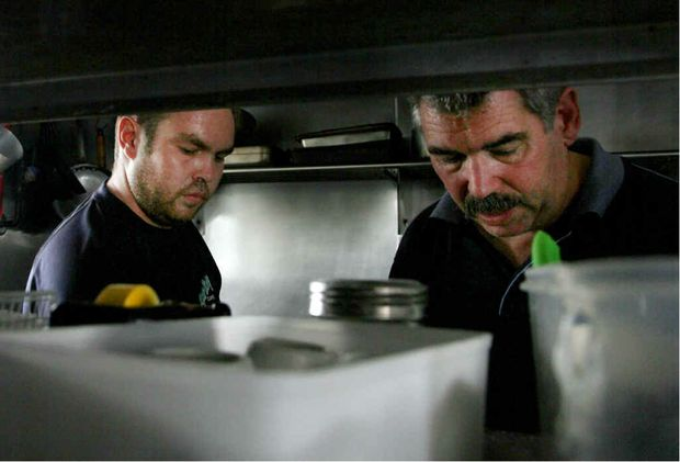 Yamba's Caperberries Cafe owners Chris and Mark Lunnon work in the dark during the black out in the lunch time period on Friday.