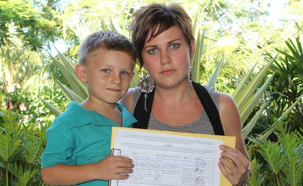 TIME TO SIGN: Bridget Middleton and her son Oliver Boldiston with the newly launched petition to floodproof the Bruce Highway between Proserpine and Mackay.