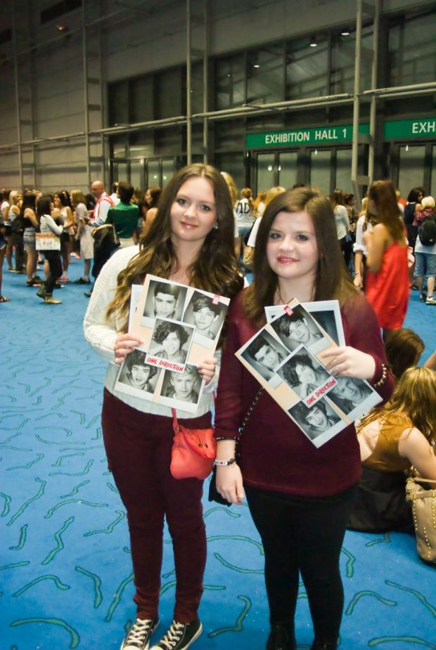 One Direction fans Sarah Payne (left) and Gemma Hill clutch their merchandise ahead of their favourite band's Brisbane concert.
