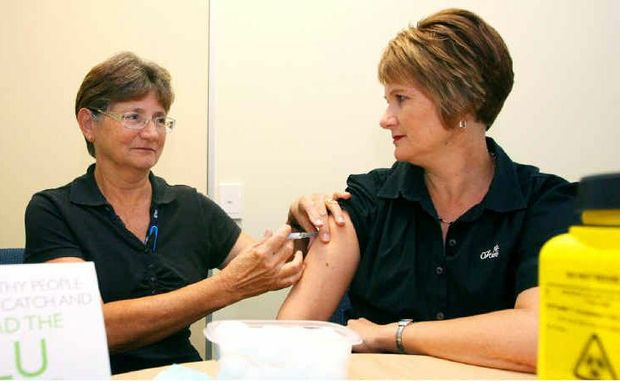 Colleen Cooper gives Karyn Dennis a flu vaccination in preparation for the coming cold season.