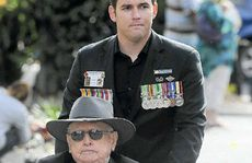 Zeek Wilkinson (back) wheels veteran Ken McFarlane down Prince St in the Grafton Anzac Day march.