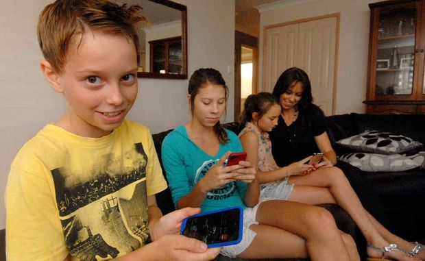 Nathan Bourdon (left) with his sisters Sarah and Renae and mother Leonie, were shocked when Mrs Bourdon was charged hundreds of dollars for an Apple game download.
