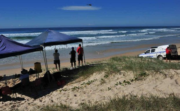 Police and surf lifesavers at the command centre help scour Peregian Beach for the missing father of two.