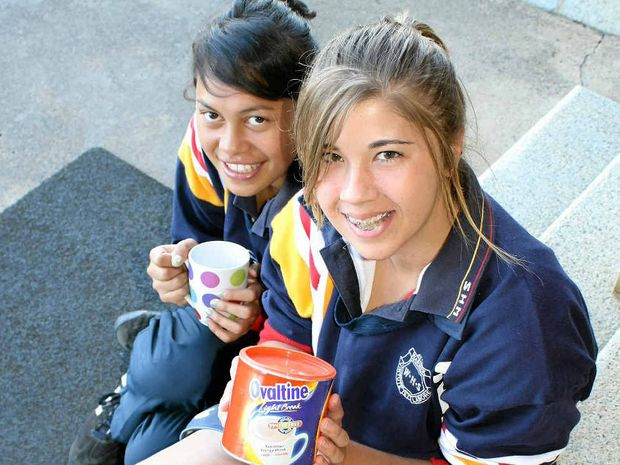 Warwick State High School Year 12 students Cassandra Connal (left) and Naomi Jensen warm up with a hot drink before school starts.