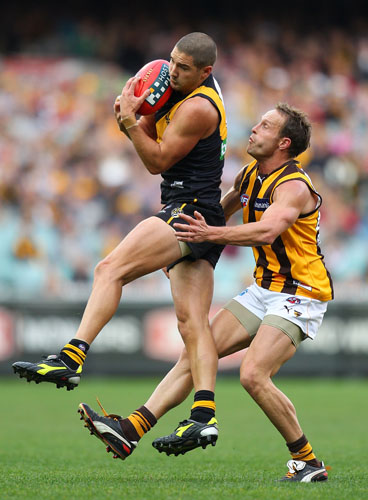 Shaun Grigg of the Tigers takes a mark in front of Brad Sewell of the Hawks during the round nine AFL match between the Richmond Tigers and the Hawthorn Hawks at the Melbourne Cricket Ground.
