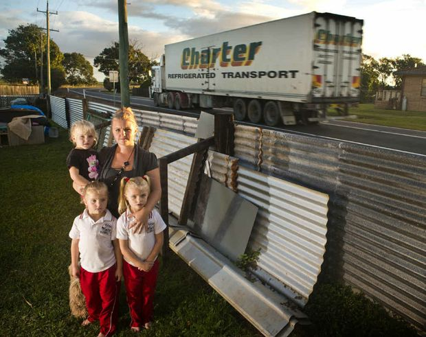 Krystal Gray with her girls Claudia, 3, Josslyn, 5, and Olivia Brown, 6, next to the fence which was destroyed by a truck on the Pacific Hwy in June 2010.