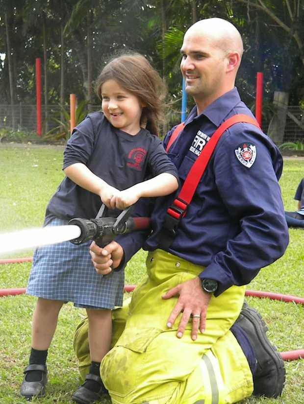 Kindergarten student Ruby Nichol and Fireman Hugh take aim at an orange safety cone.