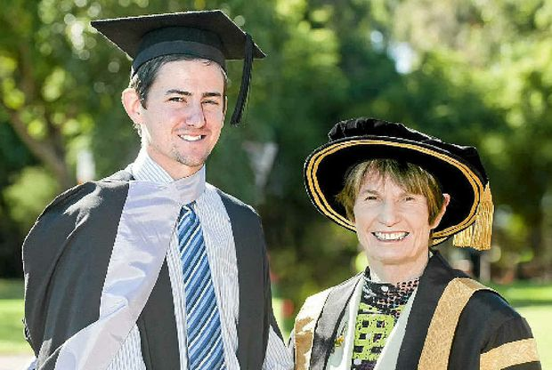 Warwick's William Reid is congratulated by USQ chancellor Bobbie Brazil after graduating with a Bachelor of Education. The former Warwick State High School student is now teaching at Wandoan State School.