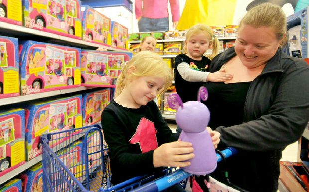 Big W's home entertainment associate Zoe Roberts (at rear) offers Rachael Buckley, with a Fijit Friends toy, Megan Buckley and their mum Julie Buckley some help in the toy section yesterday.