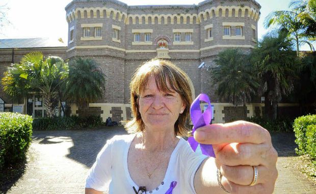 Prison officer Sandra Rendalls shows off the purple ribbons people are wearing in support of the jail workers.