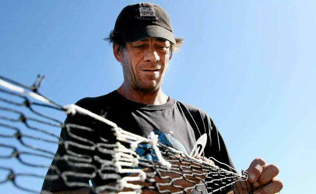 MAKING READY: Iluka mullet fisherman Mark Oestemann repairs his nets in between hauls.