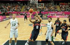 Deron Williams of the United States jumps with the ball past Antanas Kavaliauskas (L) and Linas Kleiza (2nd R) of Lithuania during the Men's Basketball Preliminary Round match between Lithuania and the United States on Day 8 of the London 2012 Olympic Games