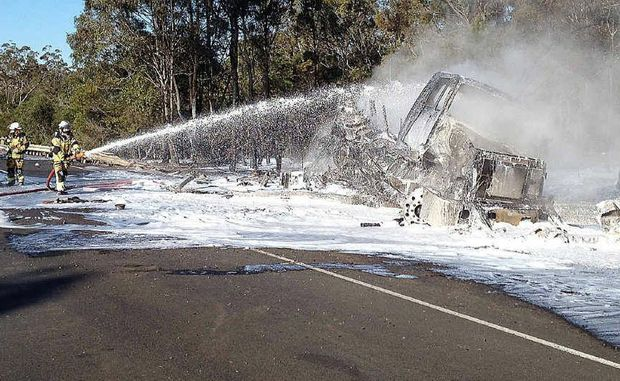Firefighters quell a fuel tanker blaze on the Bruce Hwy.