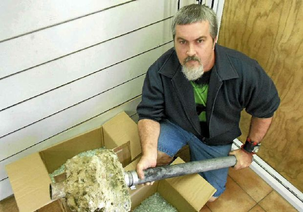 The Capricorn Model House shop manager Shane Davey with the pipe set in concrete that teens allegedly used to smash into the premises.