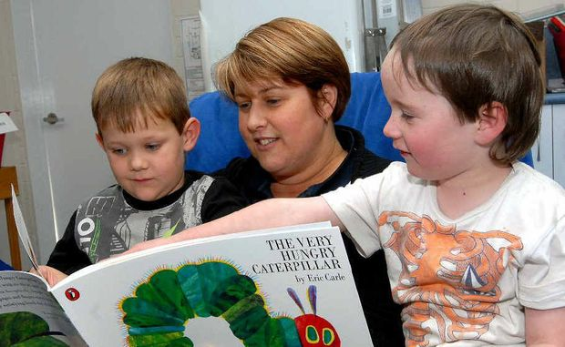 Moranbah's Simply Sunshine Childcare director Amanda Stephan reads to Jay Pietzner and Ashton Hampton. The centre cares for about 70 children.