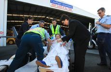 Evelyn Maidens is helped by ambulance officers into the careflight jet for the trip to St George.