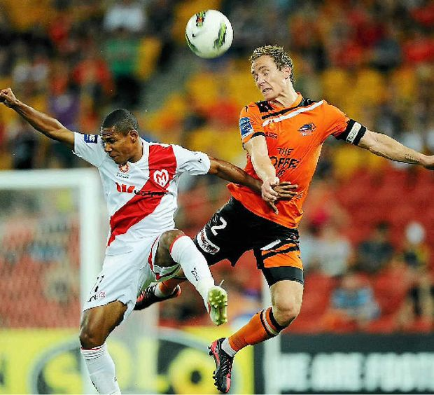 Brisbane Roar captain Matt Smith, right, climbs high for the header.
