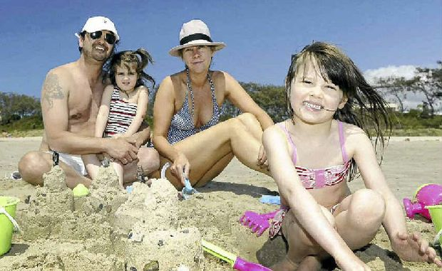 SOAKING IT UP: Paul Attard and Madelienne Anderson from Sydney enjoy Main Beach, Byron Bay, with their daughters Appley, 5, and Octavia, 3. Good weather and record crowds have boosted business figures.