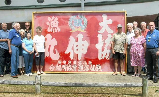 FLYING THE FLAG: Members of the Ballina Naval and Maritime Museum with the huge Japanese flag.