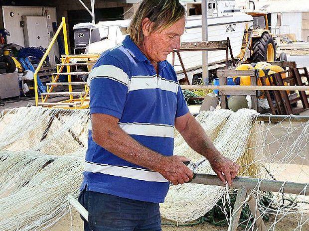 Geoff Bachmann repairs a shark net damaged by a crocodile.