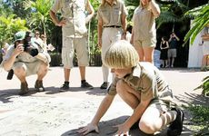 Robert Irwin puts his hands in his dad's handprints at Australia Zoo.