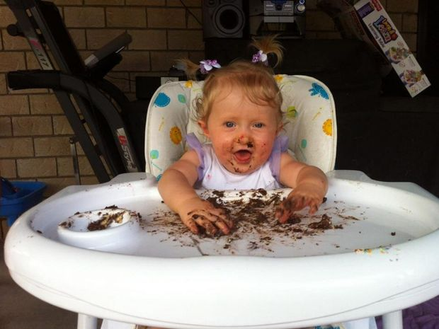 PURE JOY: Alexcia Buchanan delights in a slice of chocolate cake during her first birthday party.