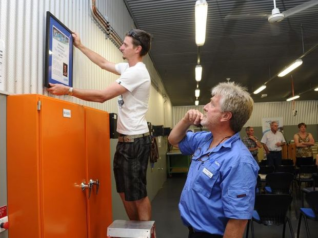 Childhood friend and long-time mate of the late Tim Whitehead, Simon Plumb, hangs a frame in the new refrigeration unit at Grafton TAFE as Electrical and refrigeration teacher Greg Williams watches on. The new refrigeration unit was named in honour of Tim Whitehead. Photo: JoJo Newby / The Daily Examiner