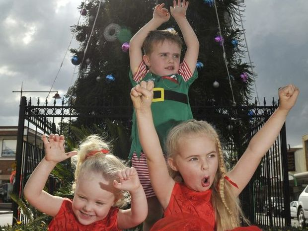 Phoebe Gilmour (3), Lochie Ryan (4) and Georgia Ryan (5) in front of large Christmas tree in the CBD.